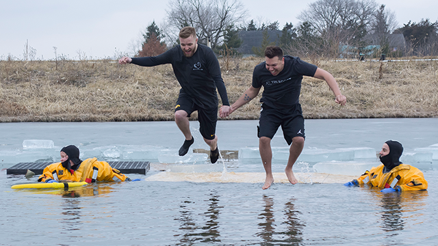 two men jumping into cold water