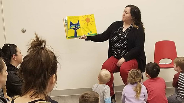 woman reading story to kids